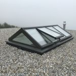 Glassatteldach mit offenen Fenster auf FLachdach